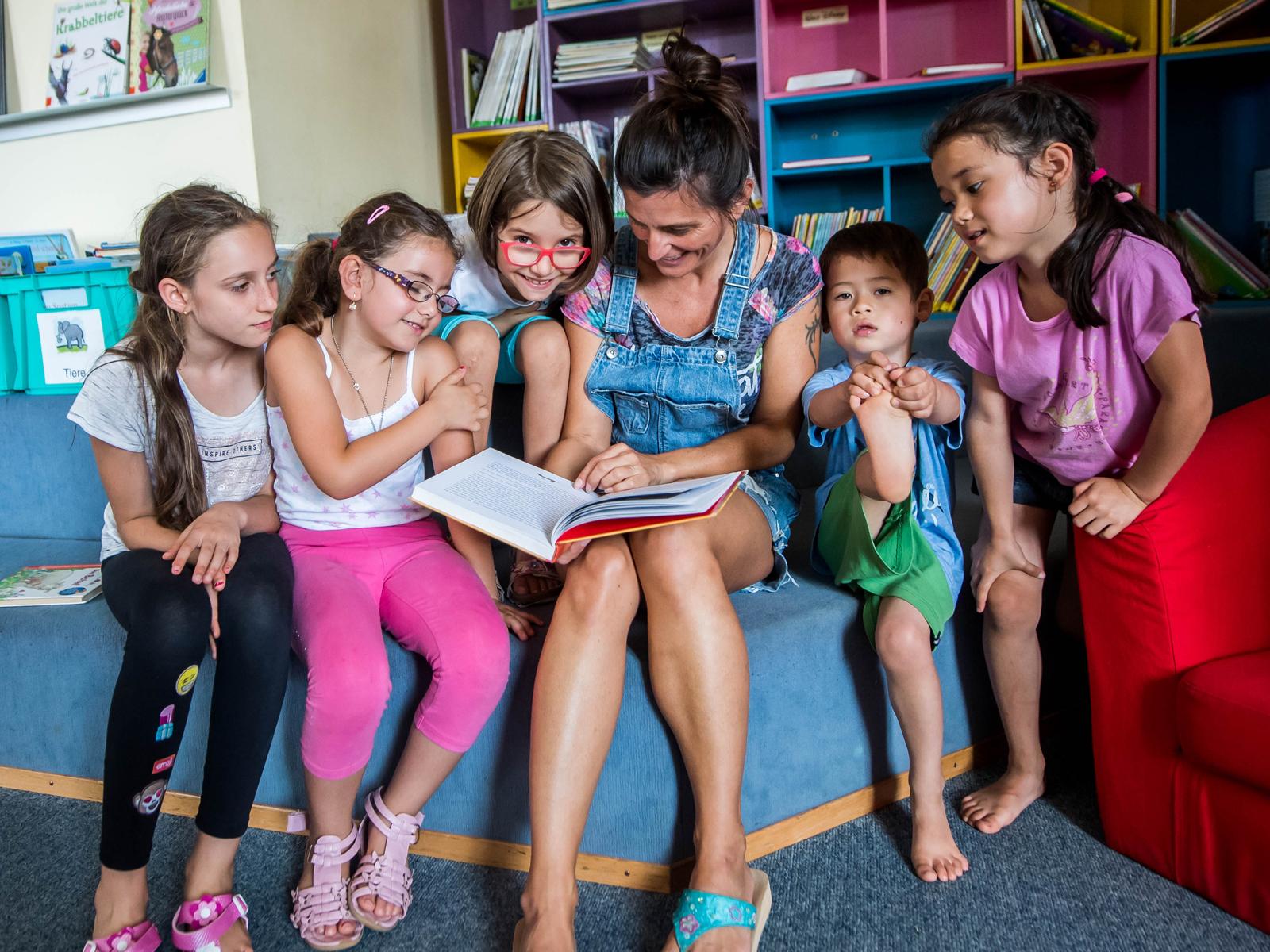 Beim Geschichtenschloss ist die Vorlesepatin von Kindern umringt, die ihren Worten interessiert lauschen