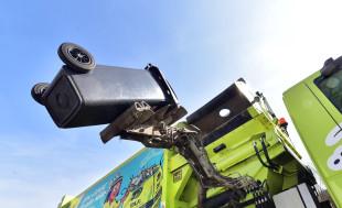 Müllauto beim Leeren einer Tonne mit automatischem Greifarm