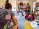 Frau umringt von Kindern beim Vorlesen in einer Bücherei