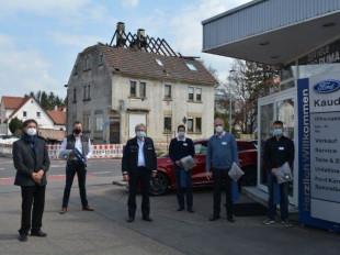 Oberbürgermeister Klaus Heininger und Erster Polizeihauptkommisar Klaus Stipp stehen mit den zwei Geschäftsführern und zwei Mitarbeitern des Autohauses Kauderer auf dem Parkplatz des Autohauses. Im Hintergrund sieht man das abgebrannte Haus.