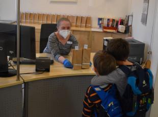 Zwei Kinder bekommen zwei Überraschungstüten an der Theke der Stadtbücherei.