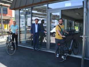 Oberbürgermeister Klaus Heininger steht mit Dirk Ringleb, Leiter des Fachbereiches Bauen und Verkehrsplaner Tobias Schwämmle stehen mit Fahrrädern an der offenen Eingangstür des Fahrradparkhauses.