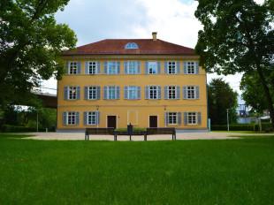 Das Eislinger Schloss mit der gelben Fassade. Davor der Park mit zwei Parkbänken und dem Brunnen.