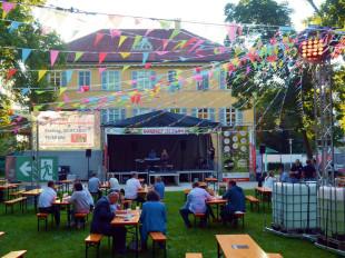 Vor dem Schloss ist eine Bühne aufgebaut. In der Luft hängen bunte Fähnchen. Besucher sitzen an Bierbänken und hören der Band zu.