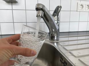 Aus einem Wasserhahn fließt Wasser in ein Trinkglas