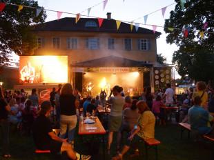 Blick in der Abenddämmerung über das Publikum hinweg auf die gelb beleuchtete Bühne.