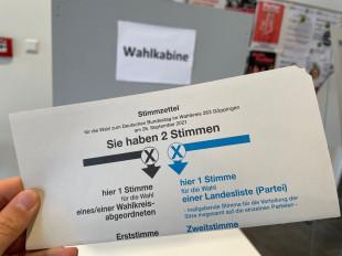 Stimmzettel und im Hintergrund die Wahlkabine