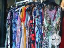 Bunte Kleider hängen vor einem Geschäft in der Innenstadt