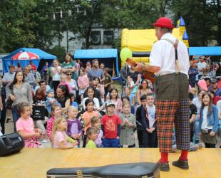 Ein Clown steht auf der Bühne im Schlosspark mit einer Gitarre. Kinder stehen vor der Bühne und schauen zu.