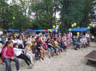 Viele Kinder sitzen im Schlosspark und schauen auf die Bühne.