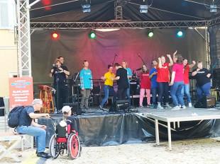 Die Band Klangspiel musiziert und tanzt auf der Bühne in bunten T-shirts.