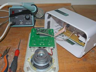 Ein Lautsprecher liegt auseinandergebaut auf einem Tisch mit Werkzeugen.