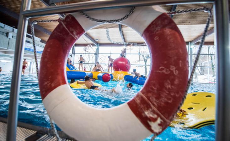 Blick durch Rettungsring auf Schwimmbecken und spielende Kinder