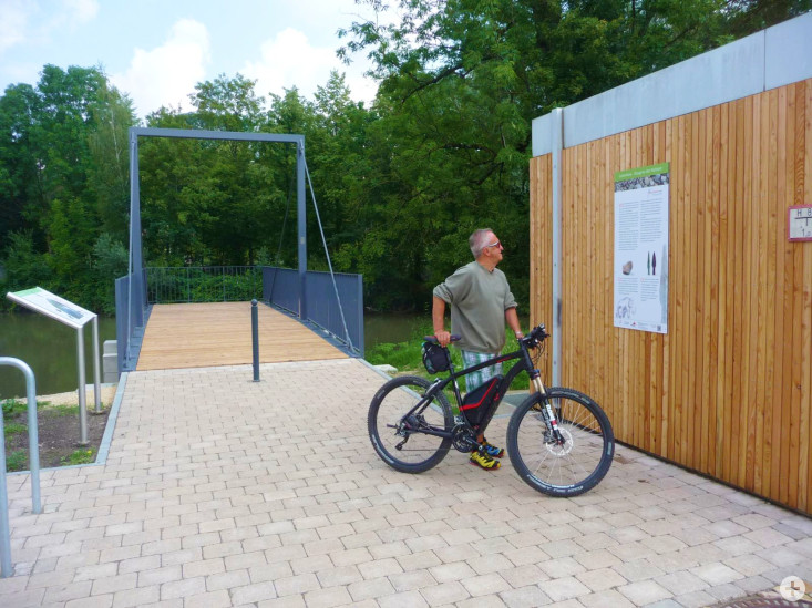 Ein Radfahrer steht an einer Infotafel am Filswehr