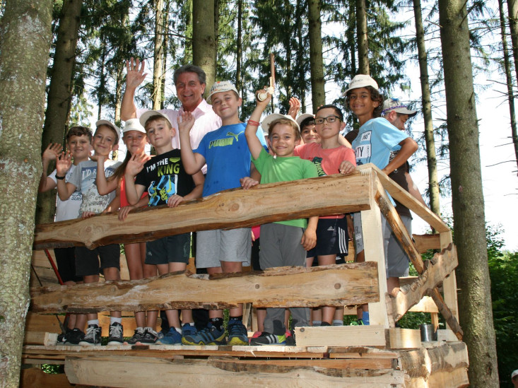 Gruppe Kinder winkt gemeinsam mit Oberbürgermeister Klaus Heininger von einer Holzplattform im Wald