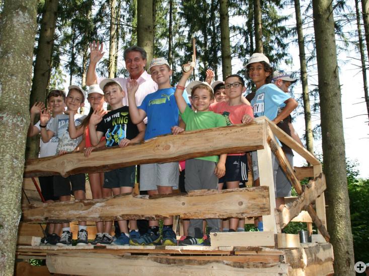 Stolz präsentieren die jungen Bauingenieure OB Klaus  Heininger die solide Bausubstand ihrer selbstgezimmerten  Hütten, die selbst einer größeren Gruppe Stand halten.