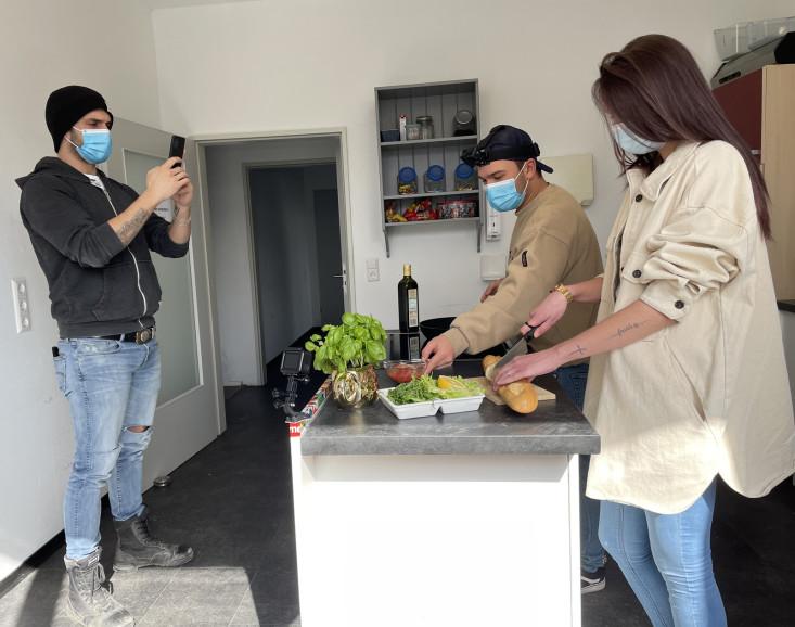 Peter Rost (links im Bild) filmt Anamaria (Auszubildende) und Samuel (Praktikant) beim Kochen im Jugendhaus