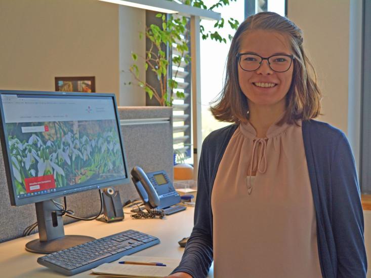 Mitarbeiterin Linda Borlinghaus steht vor ihrem Schreibtisch.