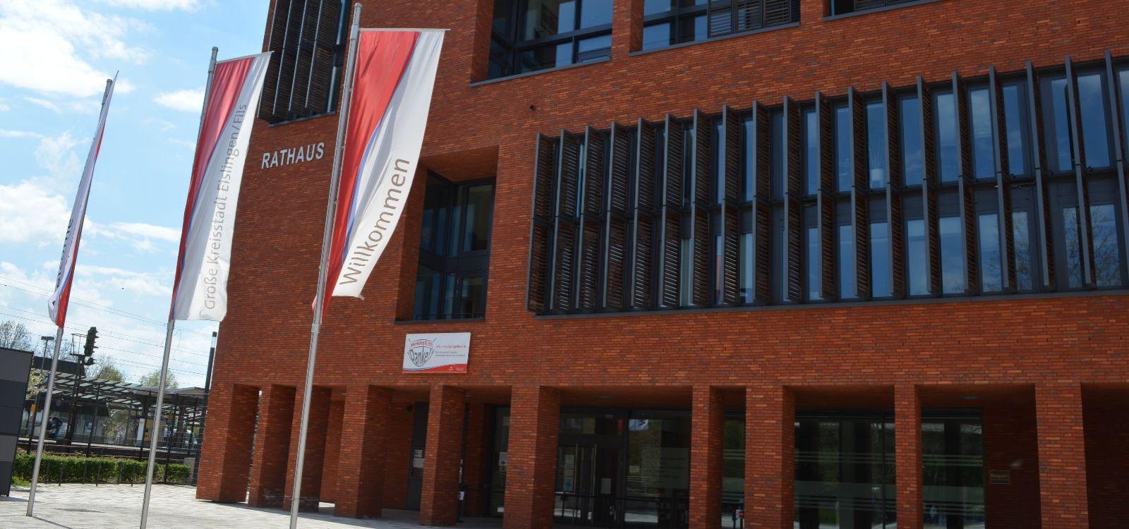 Das rote Rathaus von vorne. Davor drei Fahnen mit der Aufschrift Wilkommen. Der Himmel ist blau.