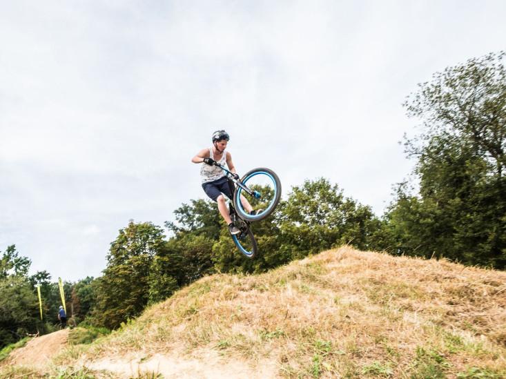 Ein BMX-Fahrer springt mit seinem Rad über einen Erdhaufen in die Luft