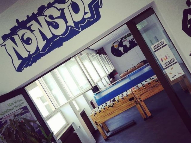 Blick in die Räumlichkeiten des Jugendhauses Nonstop: zwei Tischkicker, ein Graffiti-Schriftzug mit dem Wort Nonstop.