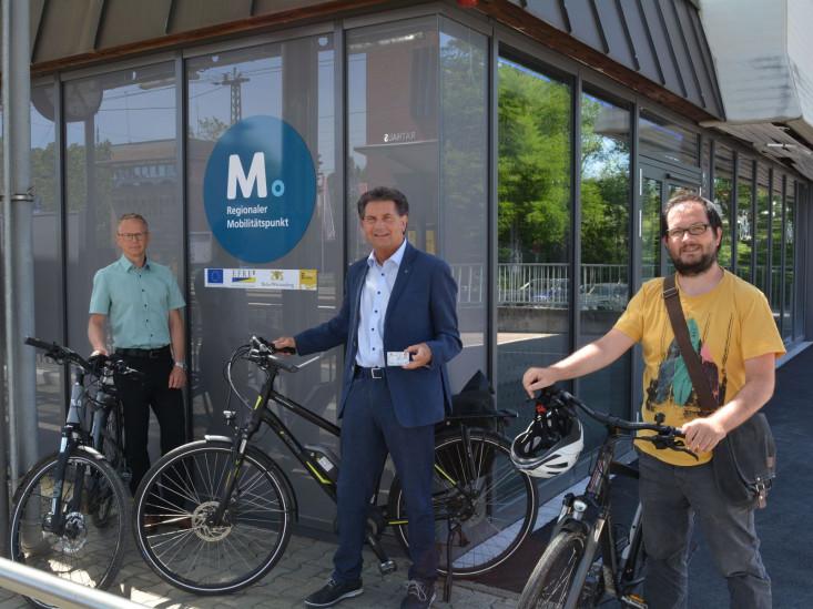 Oberbürgermeister Klaus Heininger steht mit Dirk Ringleb, Leiter des Fachbereiches Bauen und Verkehrsplaner Tobias Schwämmle stehen mit Fahrrädern vor dem Fahrradparkhaus. An der Wand das Logo vom Mobilitätspunkt und den Fördergebern.