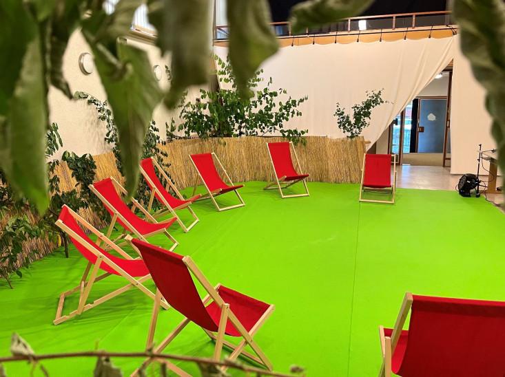 Eine Kulisse aus rote Klappstühle auf einem grünen Teppich