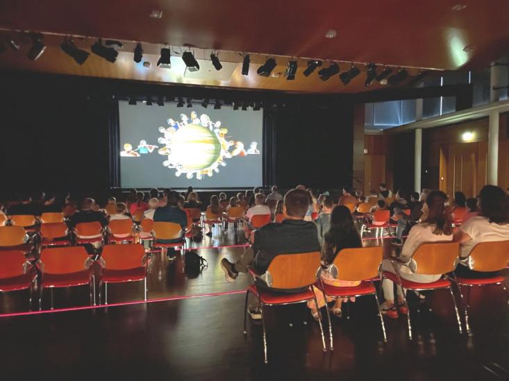 Blick aus dem Publikum auf die Leinwand der Stadthalle.