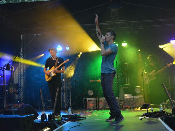 Auf der bunt beleuchteten Bühne im Schlosspark stehen ein Sänger und ein Gitarrist.