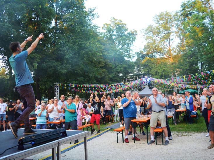 Der Sänger animiert das Publikum. Das Publikum steht und klatscht.