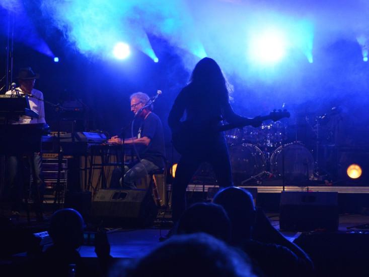 Blick vom Publikum auf die Bühne. Die Band spielt unter blauem Licht.