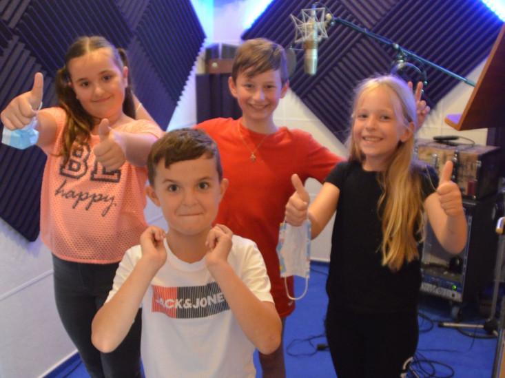 Vier Kinder im Tonstudio lachen in die Kamera und zeigen den Daumen nach oben.