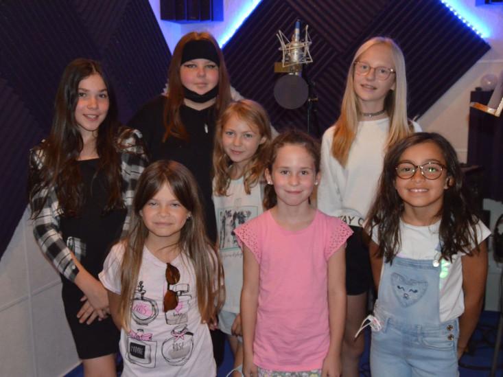 Sieben Mädchen stehen im Tonstudion und lächeln in die Kamera