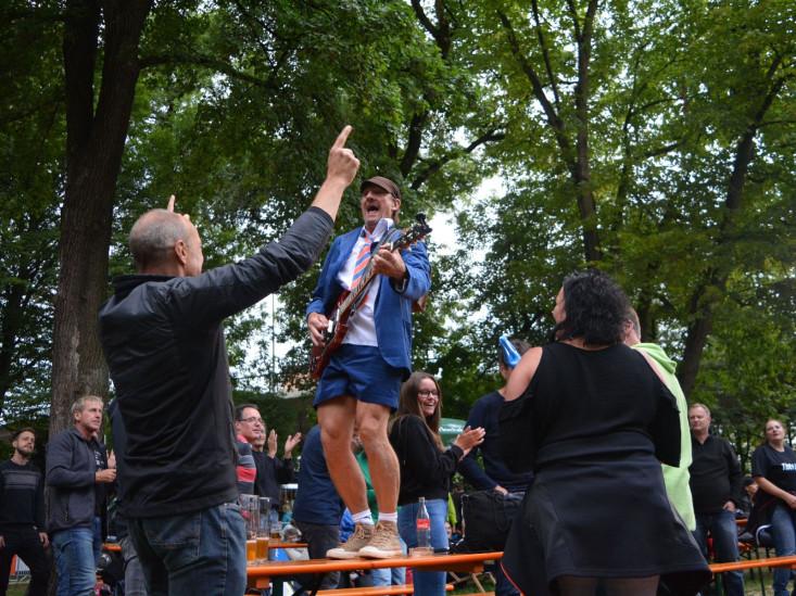 Ein Gitarrist steht auf einem Biertisch in Mitten des Publikums im Eislinger Schlosspark