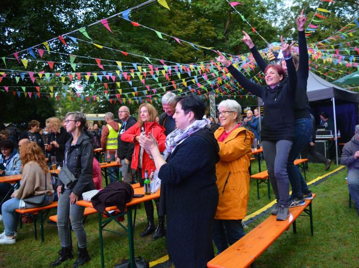 Das Publikum im Schlosspark. Teilweise stehen Menschen auf Bierbänken.
