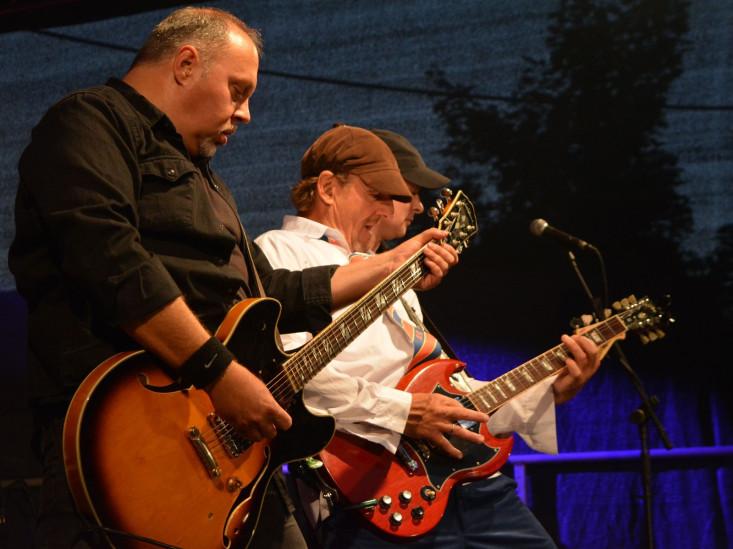 Zwei Gitarristen auf der Bühne beim Spielen.