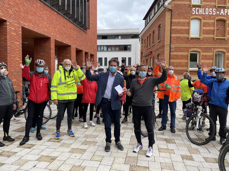 Oberbürgermeister Klaus Heininger übergibt die Spende im Briefumschlag an Vereinsvorsitzenden Klaus Riegert. Hinter den beiden stehen die Radlerinnen und Radler und winken.