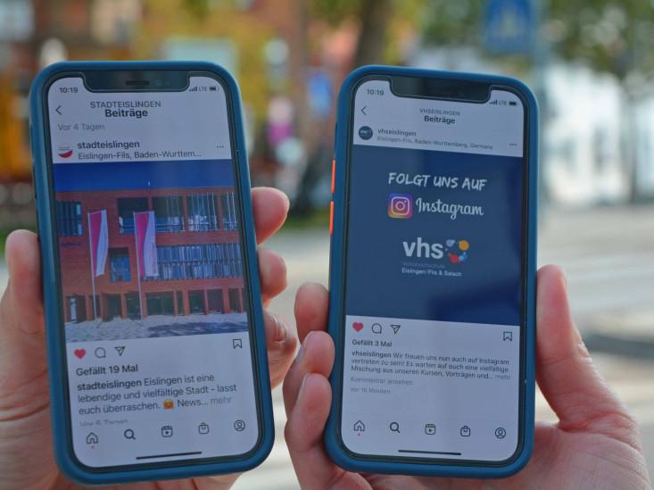 Blick auf zwei Smartphones mit den geöffneten Instagram-Profilen der Stadt und der vhs.