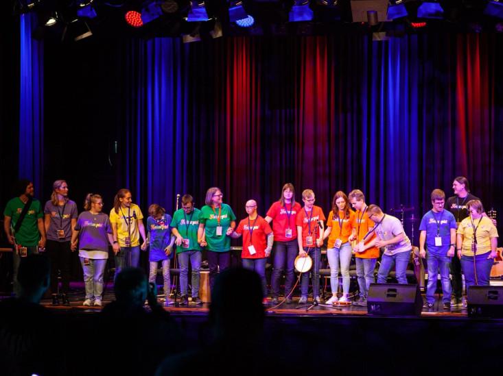 Junge Musikerinnen und Musiker stehen mit bunten T-shirts auf der Bühne und verbeugen sich