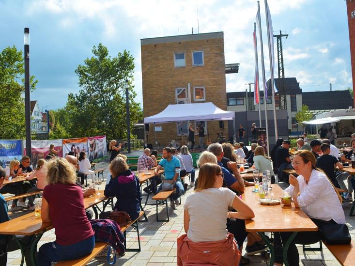 Menschen sitzen bei schönem Wetter auf Bierbänken auf dem Schlossplatz.